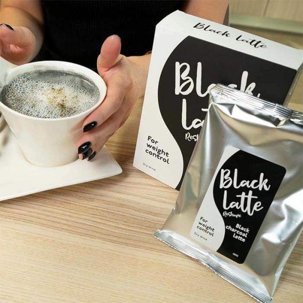 Девушка за столом пьют угольный кофе для похудения - Black Latte
