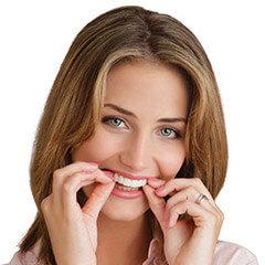 Женщина надевает на верхнюю челюсть съемные зубные виниры