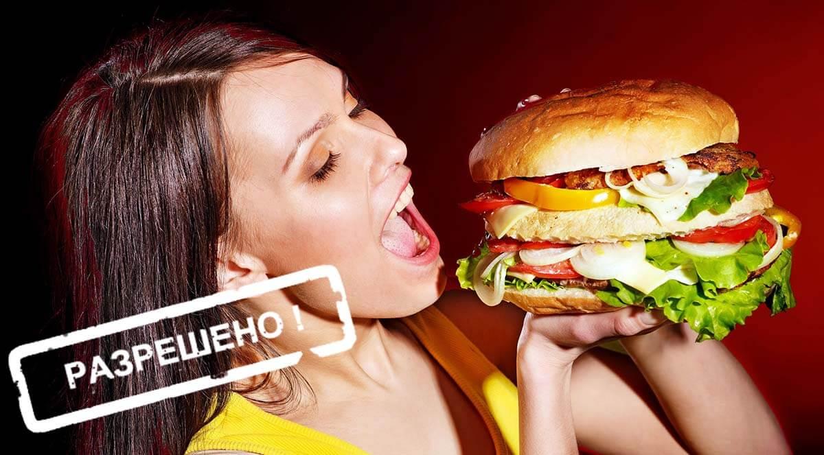 Девушка пытается съесть огромный гамбургер
