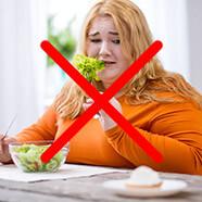 Полная девушка в оранжевой кофточке, ест салат