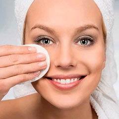Девушка с полотенцем на голове, с помощью спонжа очищает лицо