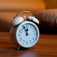 Классически будильник на деревянном столе