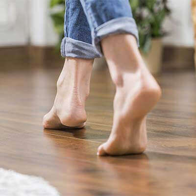 Девушка идет по линолеуму босыми ногами