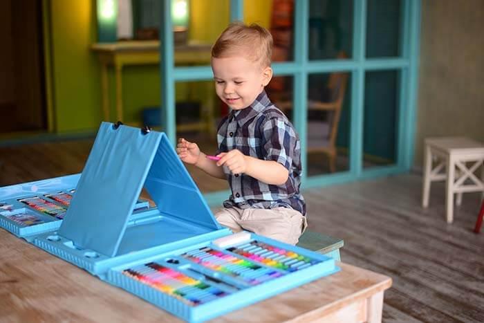 Мальчик рисует, используя детский набор для творчества синего цвета