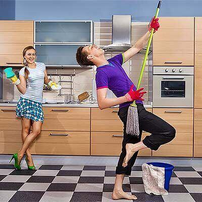 Парень и девушка делают уборку на кухни и радуются этому