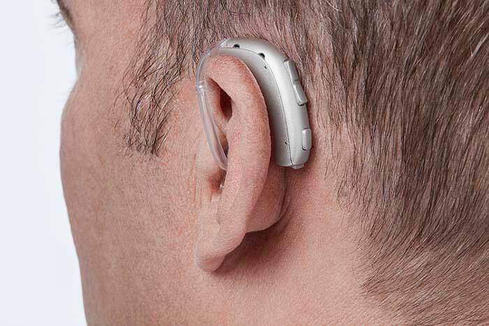 У мужчины на ухе надет слуховой аппарат Oticon Xceed