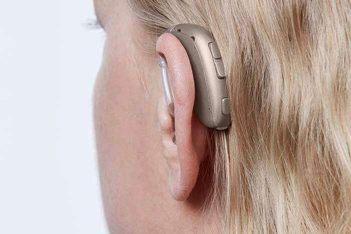 У женщины на ухе надет слуховой аппарат Oticon Xceed